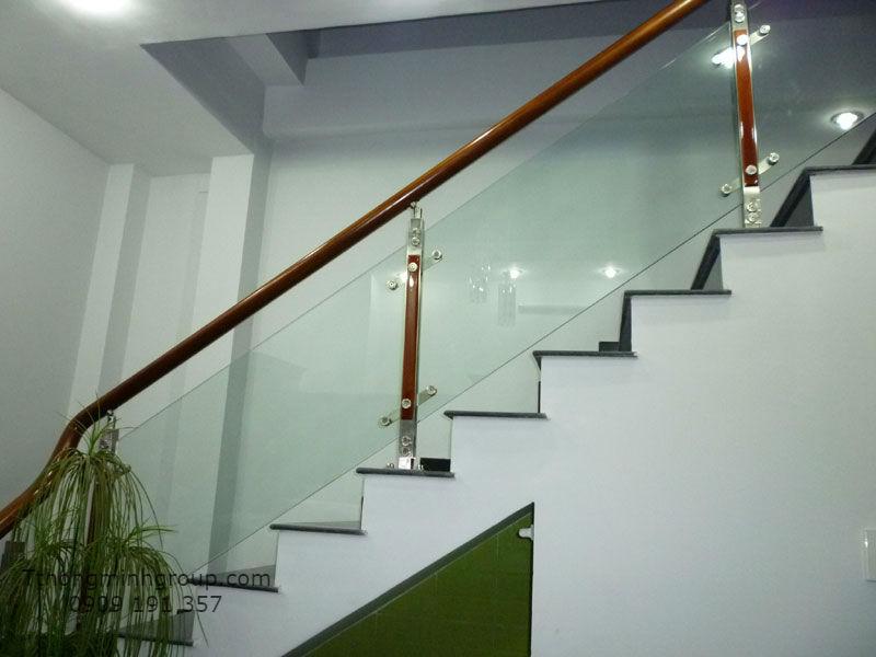 cầu thang kính cường lực có trụ, tay vịn gỗ